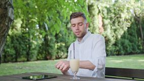 A Young Man Drinking Milkshake in the Park. A young man finishing work and drinking a milkshake in the park. Medium shot. Soft Focus stock photo