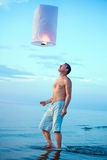 A young man with a fire lantern Stock Photography
