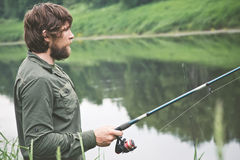 Young Man Fisherman bearded fishing with rod Stock Image