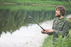 Young Man Fisherman bearded fishing with rod Royalty Free Stock Images