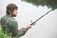 Young Man Fisherman bearded fishing with rod Stock Photo