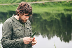 Young Man Fisherman bearded standing with knife and rod Lifestyle Stock Photos