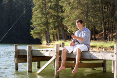 Young man fishing. On a pier Royalty Free Stock Photography