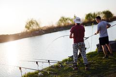 Young man fishing on a lake at sunset and enjoying hobby. Young men fishing on a lake at sunset and enjoying hobby and recreation Stock Photography