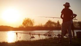 Young man fishing on lake at sunset enjoying hobby. Young men fishing on lake at sunset enjoying hobby on weekend Stock Photography