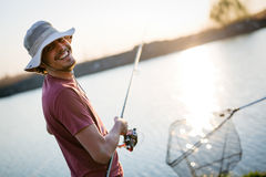 Young man fishing on a lake at sunset and enjoying hobby Stock Photo