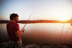 Young man fishing on lake at sunset enjoying hobby. On weekend Stock Image