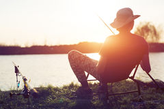 Young man fishing on lake at sunset enjoying hobby Stock Image