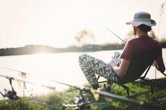 Young man fishing on lake at sunset enjoying hobby Royalty Free Stock Photography