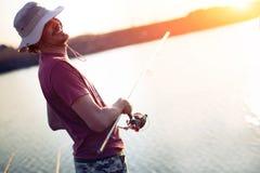 Young man fishing on lake at sunset enjoying hobby Royalty Free Stock Photo