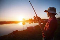 Young man fishing on lake at sunset enjoying hobby Stock Photo