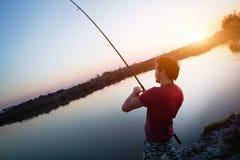 Young man fishing on lake at sunset enjoying hobby Stock Photos