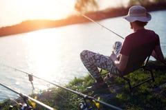 Young man fishing on lake at sunset enjoying hobby Royalty Free Stock Photos