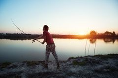 Young man fishing on a lake at sunset and enjoying hobby. And recreation Royalty Free Stock Image