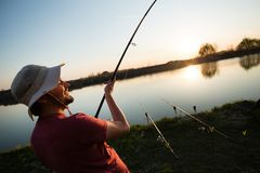Young man fishing on a lake at sunset and enjoying hobby stock photography