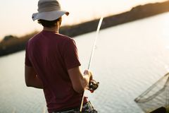 Young man fishing on lake at sunset enjoying hobby. On weekend Royalty Free Stock Image