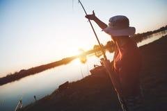Young man fishing on lake at sunset enjoying hobby. On weekend Royalty Free Stock Photos