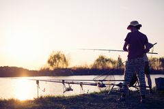 Young man fishing on a lake at sunset and enjoying hobby. Young men fishing on a lake at sunset and enjoying hobby and recreation Stock Photo