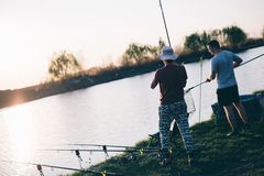 Young man fishing on a lake at sunset and enjoying hobby. Young men fishing on a lake at sunset and enjoying hobby and recreation Royalty Free Stock Photo