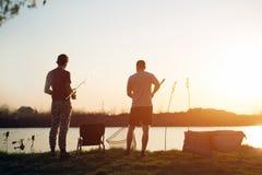 Young man fishing on lake at sunset enjoying hobby. Young men fishing on lake at sunset enjoying hobby on weekend Stock Image