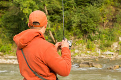 A young man fishing in a mountain river royalty free stock image