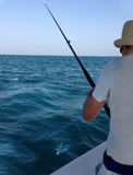 Young man fishing on a ocean Royalty Free Stock Photography