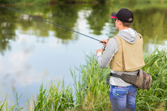 A young man fishing. Outdoor recreation. Fishing on a beautiful river. Photos for magazines, posters and Web sites Stock Photo