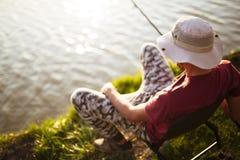 Young man fishing at pond and enjoying hobby Stock Photos