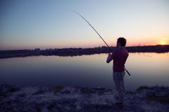 Young man fishing at pond and enjoying hobby. Activities Royalty Free Stock Photo