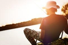 Young man fishing at pond and enjoying hobby Royalty Free Stock Images