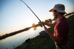 Young man fishing at pond and enjoying hobby royalty free stock images