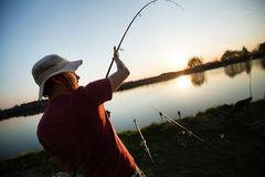Young man fishing at pond and enjoying hobby. Activities Royalty Free Stock Photos