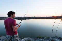 Young man fishing at pond and enjoying hobby. Activities Stock Image