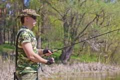 Young man fishing. On a summer day Royalty Free Stock Photos