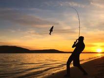 Young man fishing at sunset. Young man fishing on a lake at sunset Royalty Free Stock Photo