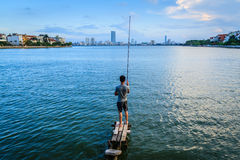 Young man fishing on west lake Stock Photography