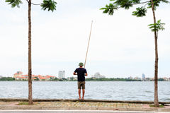 Young man fishing on West lake Royalty Free Stock Image