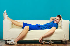 Young man fit body relaxing on couch after training Royalty Free Stock Images