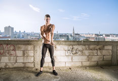 Young man fit stretching arm building outdoors model city backgr Royalty Free Stock Image