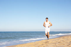 Young Man In Fitness Clothing Running Along Beach. Smiling Royalty Free Stock Photos