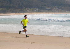 Young Man In Fitness Clothing Running Along Beach Royalty Free Stock Photography