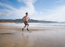 Young Man In Fitness Clothing Running Along Beach Royalty Free Stock Image