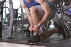 Young man with fitness tracker tying shoelaces. In gym Royalty Free Stock Photography