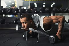 Young man fitness workout, push ups or plank. Young african-american man workout in fitness club. Black guy making plank or push ups exercise on dumbbells royalty free stock photo