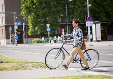 Young man with fixed gear bicycle on crosswalk Stock Image