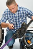 Young Man Fixing Bicycle Stock Image