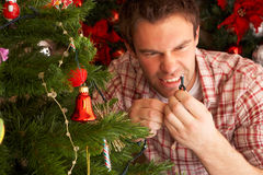 Young man fixing christmas tree lights at home Stock Photography