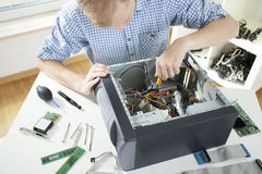 Young man fixing computer. On his own Royalty Free Stock Photos