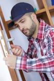 Young man fixing door Stock Photo