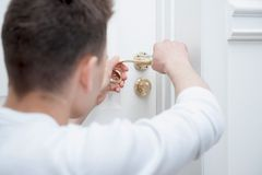 Young man fixing the door handle Stock Photos